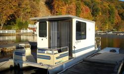 26 ft Lil Hobo Houseboat with Nissan 50 hp outboard and double axle trailer. Boat features a gas stove, refrigerator (gas & elec), fresh water system, private bathroom toilet, sleeper sofa, and additional conversion bed, front deck, rear deck, and ladder
