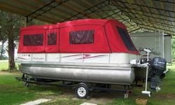 the L-shape settee. There is plenty of storage under everyone of the settees, forward and aft. The bimini is almost brand new as well as the bimini's rollup sleeve. And the boat has a cover that is in good shape.The single-axle trailer has a spare tire,