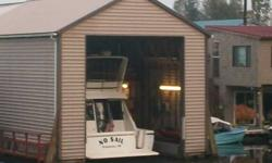 Boathouse is 1100 sq. feet living space with 40 ft boat slip inside the house structure. House is 28' x 80'. One large bedroom and two bathrooms. Two stories. Large covered outdoor deck with outside kitchen. Home has water furnace heat pump that is very