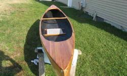 Beautiful cedar stripped canoe 12 foot. This boat is constructed with 1/8 inch cedar strips covered on the exterior with 6 oz fiberglass. The interior is 6 oz Kevlar painted black. The boat has a cherry wood cane seat and foot peg. Tumble home shear with